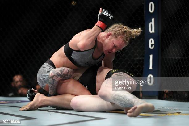 Holly Holm punches Megan Anderson of Australia in the third round in their featherweight bout during the UFC 225 Whittaker v Romero 2 event at the...