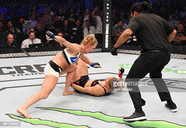 Holly Holm punches Ronda Rousey in the second round of their UFC women's bantamweight championship bout as referee Herb Dean looks on during the UFC...