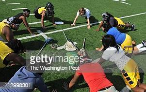 Holly McGarvie top middle leads her team in a round of pushups to get their attention during a Ballou girls' lacrosse practice at Ballou High School...