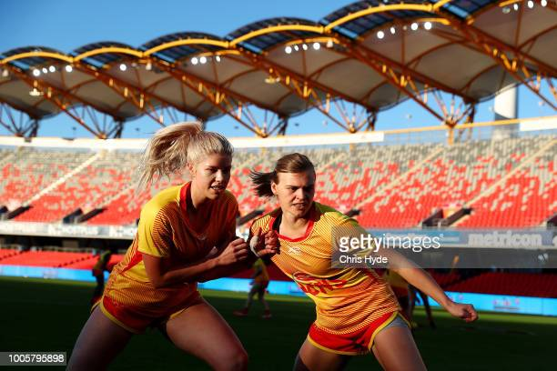 Holly Mirfield and Emma Aeschlimann of the Suns warm up before the AFLW Winter Series match between the Gold Coast Suns and the Brisbane Lions at...