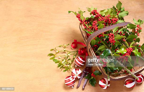 Holly Mistletoe and Christmas baubles on wood.