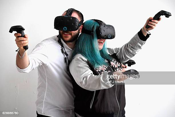 Holly Morton and Piotr Pyrchala try out gaming headsets at Scotlands First Virtual Reality Arcade on November 30, 2016 in Edinburgh, Scotland. Using...