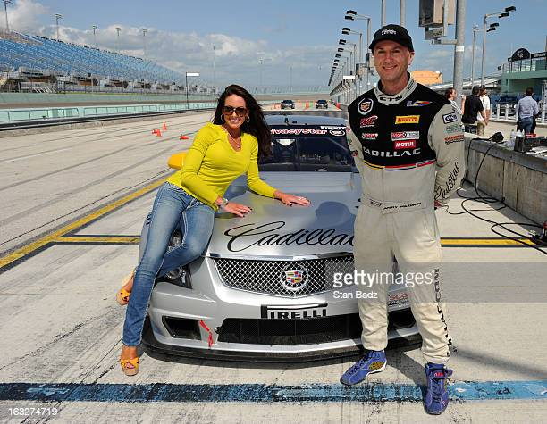 Holly Sonders host of Morning Drive on the Golf Channel and Andy Pilgrim driver for Team Cadillac pose for a photo after taking a ride in a Cadillac...