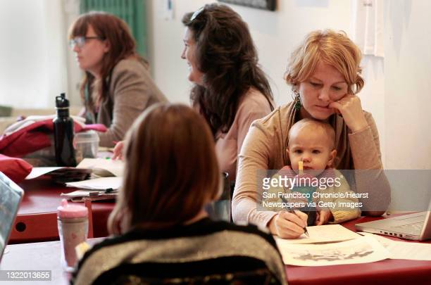 Holly Wach works on her pen and ink drawings as her 18 month old daughter Morena Scetta sticks close by on Wednesday Dec. 12, 2012 in Berkeley,...