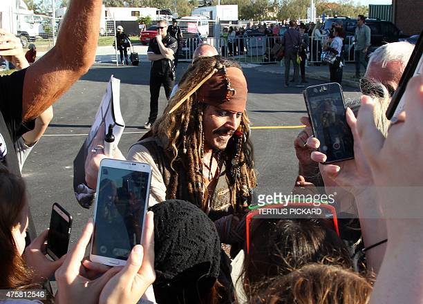 Hollywood actor Johnny Depp dressed as Captain Jack Sparrow from the Pirates of the Caribbean film franchise greets fans after returning from a day...