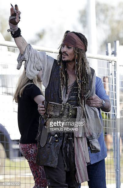 Hollywood actor Johnny Depp dressed as Captain Jack Sparrow from the Pirates of the Caribbean film franchise waves to fans after a day on the film...