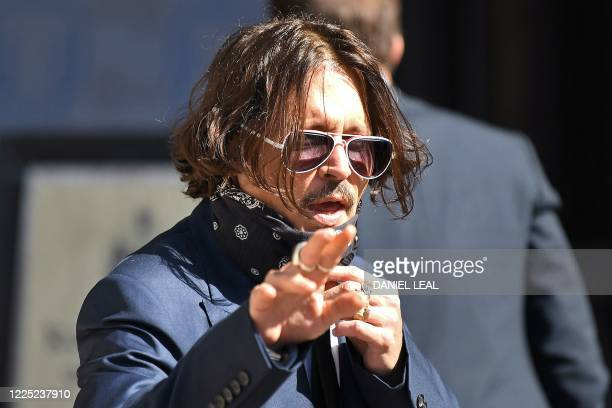 Hollywood actor Johnny Depp, wearing a face mask or covering due to the COVID-19 pandemic, arrives on the first day of his libel trial against News...