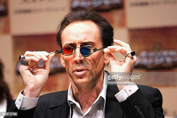 Hollywood actor Nicolas Cage holds coloured glasses up to his face during a press conference to promote his latest film National Treasure during a...