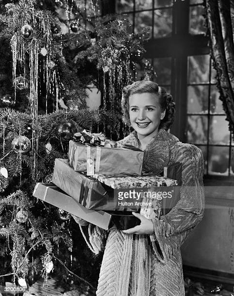 Hollywood actor Priscilla Lane stands beside a Christmas tree with an armful of holiday presents