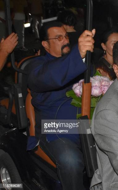 Hollywood actor Steven Seagal and his wife Erdenetuya Seagal are on their way to a private village by a caddie cart following their arrival on an...