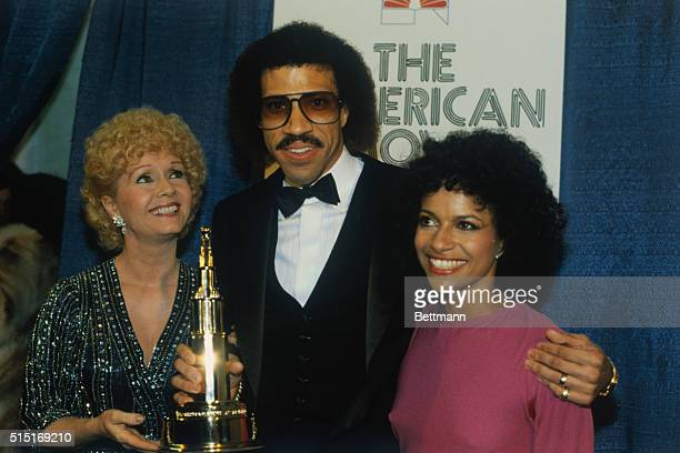 Actress Debbie Reynolds and Debbie Allen congratulate Lionel Ritchie for winning his American Film Awards trophy for the Best Original Theme Endless...