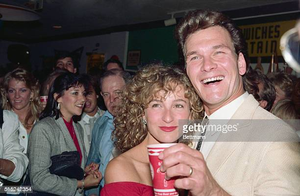 Actress Jennifer Grey gives a wink and a wave to cameras as she and her costar Patrick Swayze attend a party following the showing of their latest...