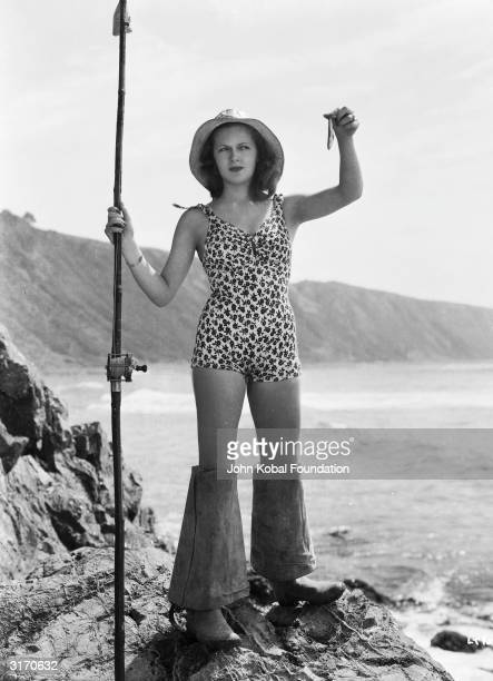 Hollywood actress Lana Turner shows off her catch dressed in a floral patterned swimsuit and waders