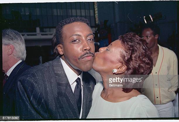 Arsenio Hall gets a 'break a leg' kiss from his mother Annie Hall as he attends the premiere screening of Coming To America in which he and Eddie...