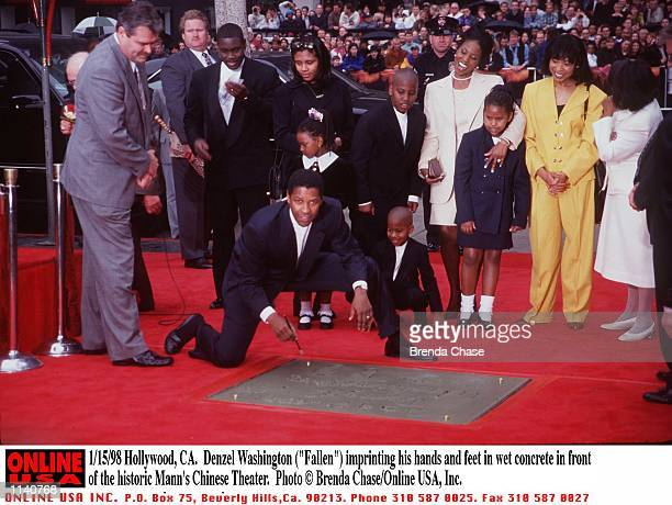 Hollywood CA Denzel Washington imprinting his hands and feet in wet concrete in front of the historic Mann's Chinese Theater