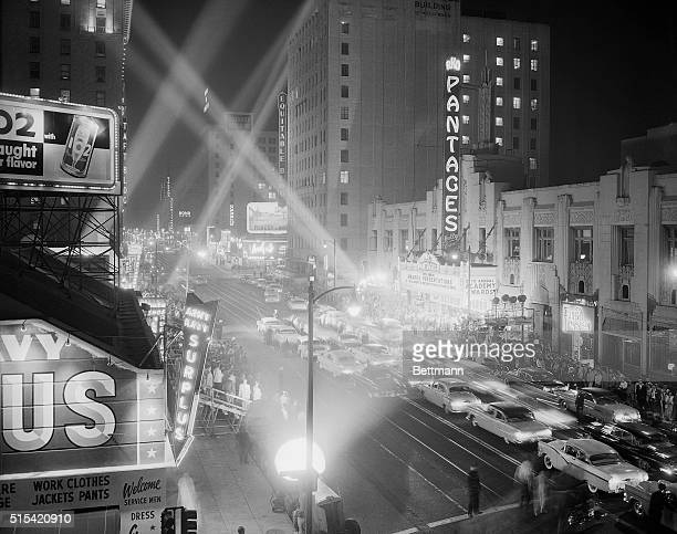 3/21/1956 Hollywood CA Giant searchlights pierce the sky and Hollywood Boulevard teems with life as crowds jam the area of the RKO Pantages Theatre...