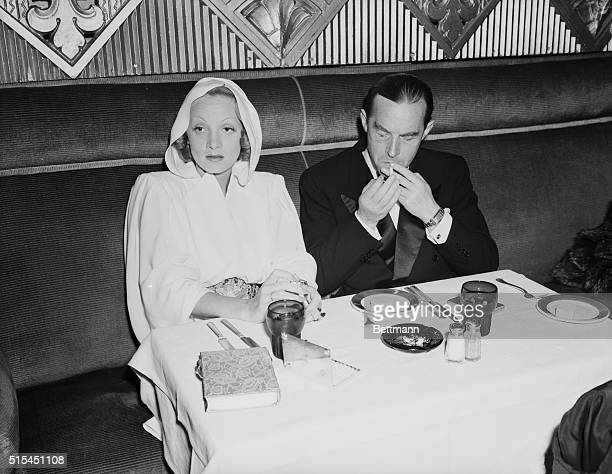 Hollywood, CA-: Marlene Dietrich and Erich Maria Remarque attending the recent premiere of the film Juarez. They are shown seated at a table,...
