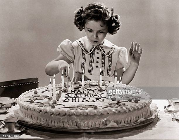 4/23/1938 Hollywood CA Shirley Temple with her birthday cake which tells the story of the little film star's ningh birthday She took time off from...