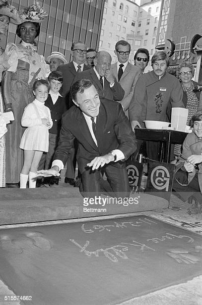 Motion picture star and director Gene Kelly smiles after placing his handprints in cement in the forecourt of the Grauman's Chinese Theatre Kelly...