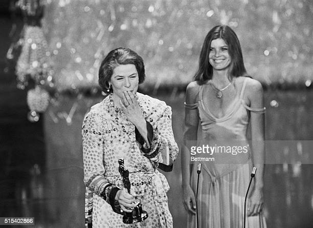 Actress Ingrid Bergman throws a kiss to the audience as presenter Katherine Ross stands behind her as she was announced the winner of the Best...