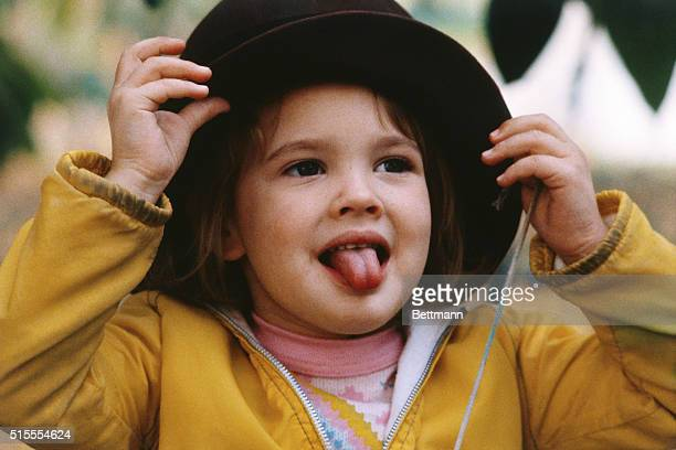 Hollywood, California: Into her own world of make believe, Drew Barrymore imagines she's a grownup as she tries on one of her mother's hats recently.