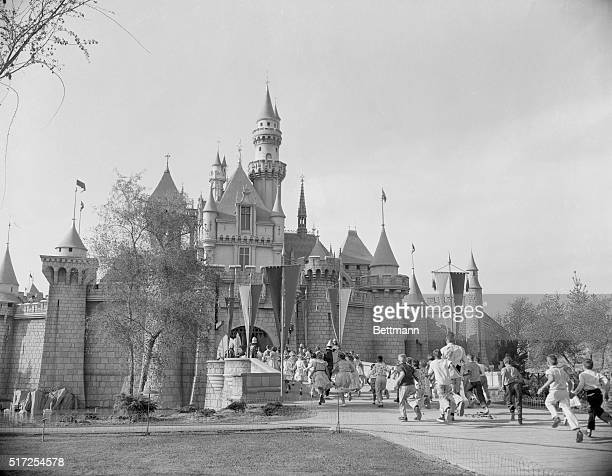 Hollywood celebrities and their children helped to make the huge opening day crowd at Disneyland. Here, a large group of them rush into Sleeping...