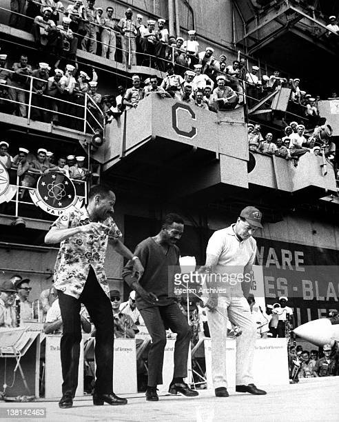 Hollywood comedian Bob Hope , wearing a baseball cap, joins dancing legends The Nicholas Brothers during Hope's USO Christmas show aboard the USS...