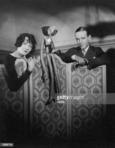 Hollywood dancer singer and film actor Fred Astaire and his sister Adele Astaire standing behind a screen and holding a doll