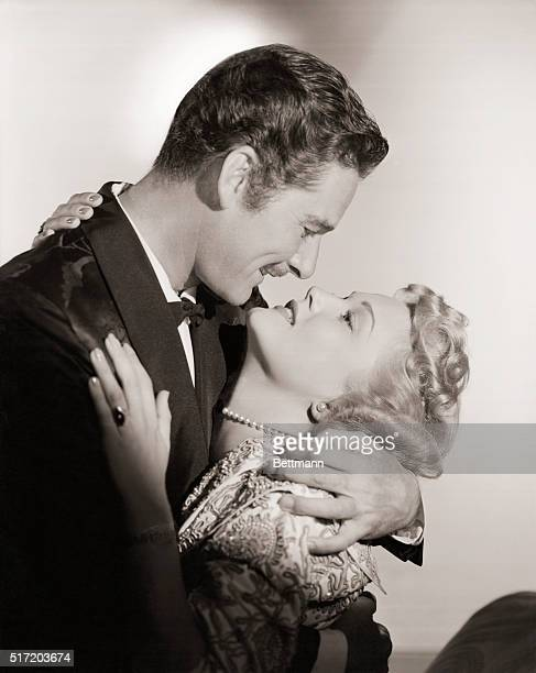Errol Flynn swashbuckling hero of the motion picture screen engages in a passionate love scene with Patrice Wymore during the filming of one of their...