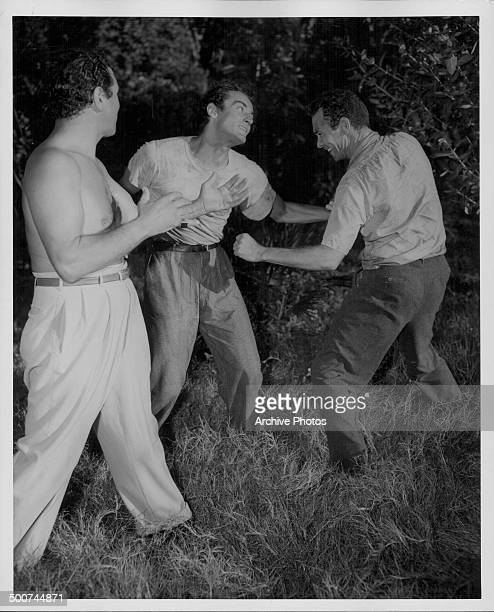 Hollywood fight expert Johnny Indrisano giving pointers to actors Vittorio Gassman and Barry Sullivan on the set of the movie 'Cry of the Hunted' 1953