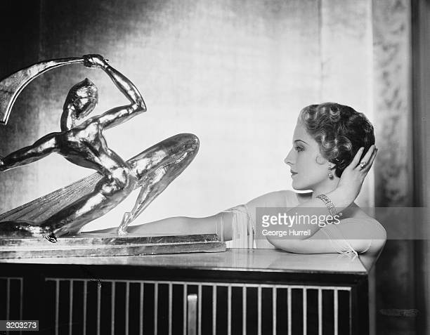 Hollywood film actress Norma Shearer contemplates a statuette of a scimitarwielding man
