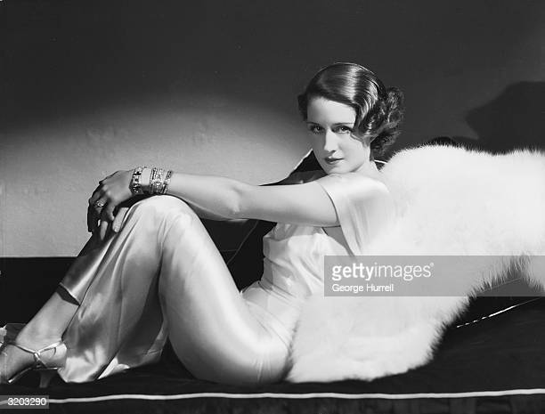 Hollywood film actress Norma Shearer reclining in a satin dress