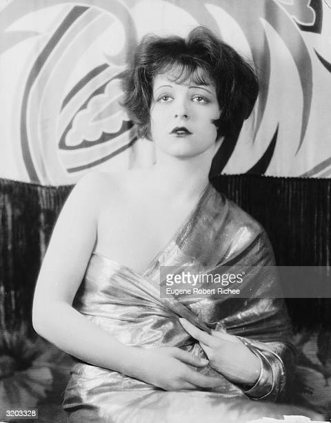 Hollywood film star, Clara Bow in a shiny, off-the-shoulder dress.