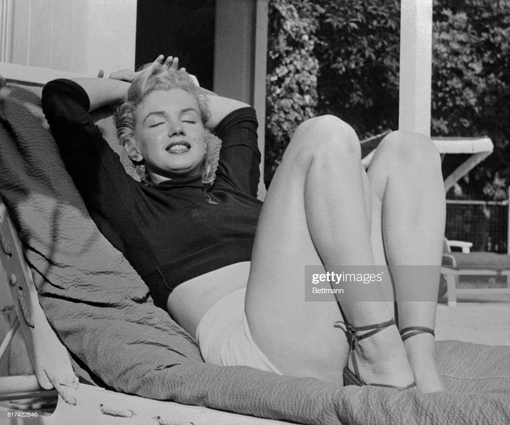 Hollywood film star Marilyn Monroe relaxes on her terrace, looking beautifully content. Actor Hugh Marlowe told the voluptuous actress that she needn't worry becuase she's being typed as a sexy girl. Marlowe's theory is that one 'Only becomes a real success when you're a specialist, 'so Marilyn is 'Lucky to be born that way.' Whether Marilyn is typed or not, she surely doesn't look worried.
