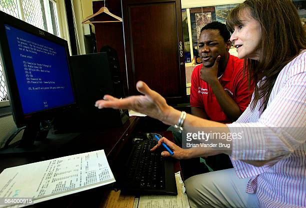 Hollywood High School college counselor Judy Campbell, right, talks with junior Deon Goggins who grimaces as he eyes his CSU GPA on a computer screen...