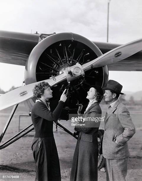 Hollywood Goes Air Minded Amelia Earhart shows Myrna Loy and Roscoe Karns the new controllable pitch propeller on her Lockheed Vega in which it is...