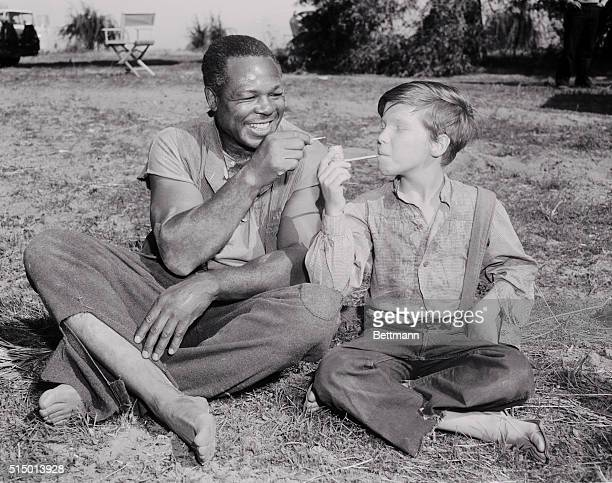 Light heavyweight boxing champion Archie Moore is shown with actoryoungster Eddie Hodges in a scene from MGM's film version of Huckleberry Finn Moore...