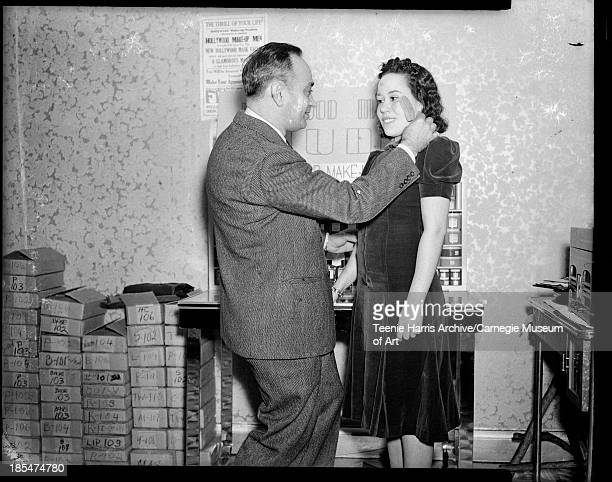 'Hollywood MakeUp Man' Harry L Warner using brush to apply makeup to woman wearing dark puffed sleeve velvet dress with pleated skirt standing in...
