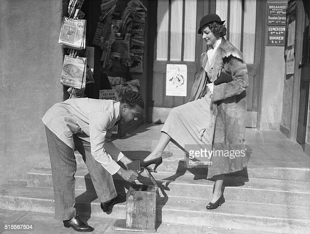 """Hollywood: Miss Betty Furness, one of R. K. O.'s newest starlets, pauses long enough to have her shoes shined by Hollywood's famous bootblack """"Rudy."""""""