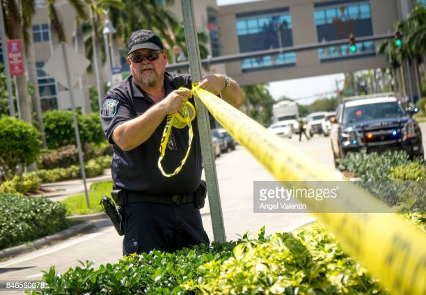 Hollywood Police Department officer wraps crime scene tape around a perimeter surrounding a rehabilitation center where six patients were found dead...