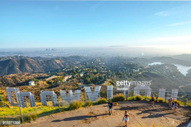 hollywood sign and hikers with los angeles in the background - mulholland drive stock photos and pictures