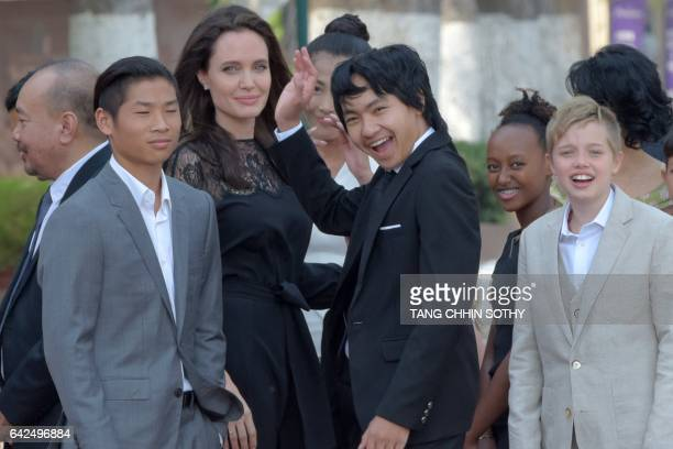 Hollywood star Angelina Jolie and her children including Maddox JoliePitt gesture to media in front of the royal residence for a meeting with...
