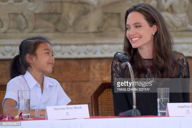 Hollywood star Angelina Jolie interacts with Cambodian child actress Sareum Srey Moch during a press conference at a hotel in Siem Reap on February...