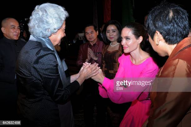 Hollywood star Angelina Jolie pays respect to Cambodian former queen Monique as Cambodian King Norodom Sihamoni looks on during the premiere of...