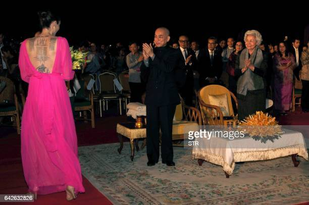 Hollywood star Angelina Jolie walks past Cambodian King Norodom Sihamoni and former queen Monique during the premiere of Jolie's new film 'First They...