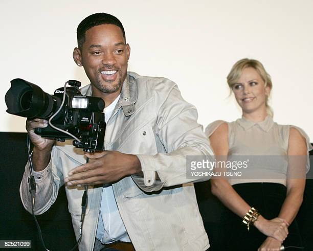Hollywood star Will Smith uses a press photographer's camera for a joke during the premier of his latest movie Hancock at a Tokyo theater on August...