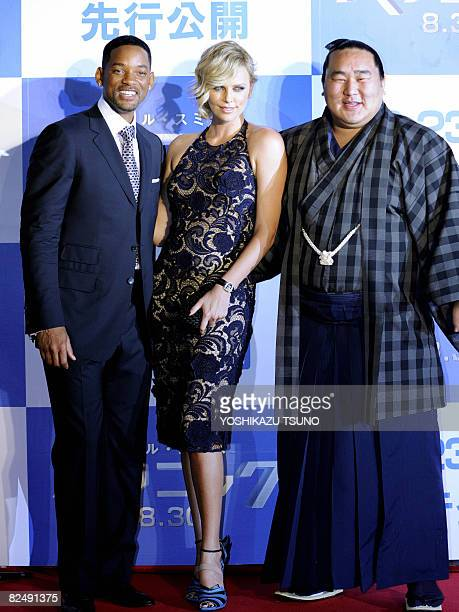 Hollywood stars Charlize Theron and Will Smith pose with Mongolian sumo grand champion Asashoryu for press representatives on a red carpet at the...