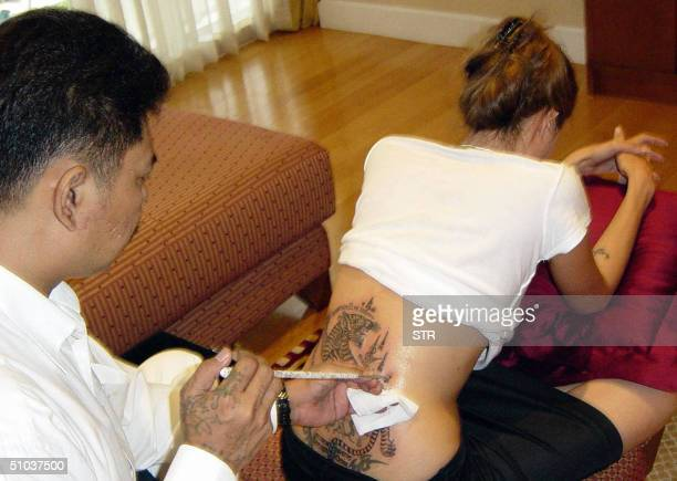 Hollywood superstar Angelina Jolie gets a tattoo from Thai tattoo master Sompong Kanphai at an apartment in Bangkok 08 July 2004 Jolie had a tattoo...