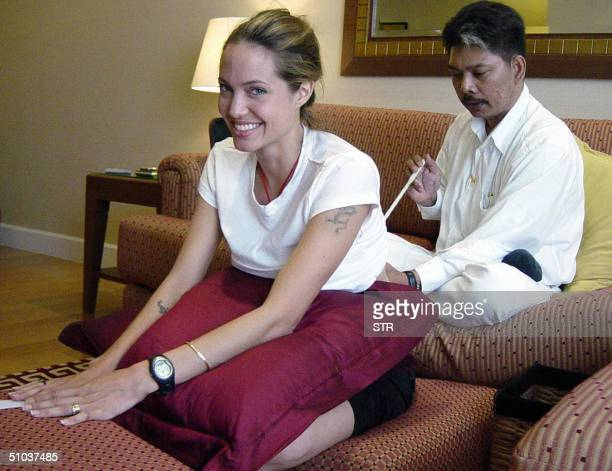 Hollywood superstar Angelina Jolie smiles while getting a tattoo from Thai tattoo master Sompong Kanphai at an apartment in Bangkok 08 July 2004...