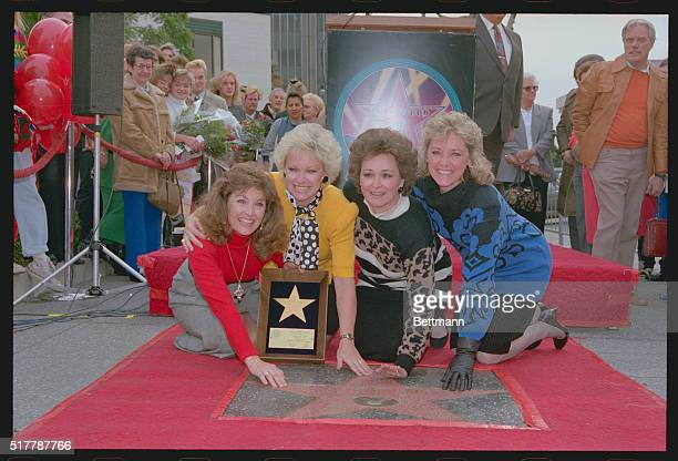 The Lenon Sisters Kathy Janet Peggy and Dianne smile for cameras as they put their hands on their star on the Hollywood Walk of Fame The sisters...
